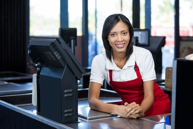 Female staff sitting at cash counter Premium Photo