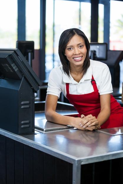 Female staff sitting at cash counter Premium Photo