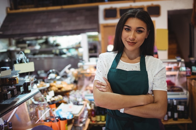 Female staff standing with arms crossed in super market Free Photo
