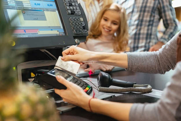 Female staff using credit card terminal at cash counter Free Photo