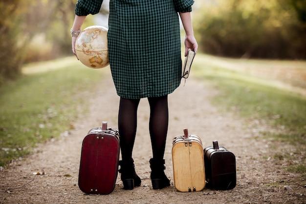 聖書と地球儀を持ってスーツケースの近くの空の道に立っている女性 無料写真