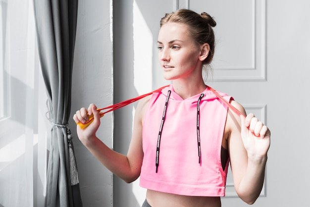 Female standing with skipping rope in hands Free Photo