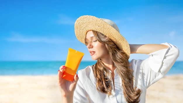 Female in straw beach hat holding sunblock spf cream on rocky sunny backdrop. protection from uv sun rays, summertime vacation holiday. european ethnicity. Premium Photo
