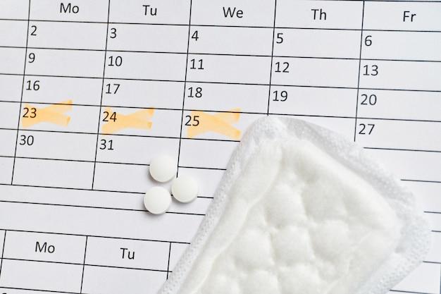 日付マークとホルモン剤のカレンダー上の女性のストリップ Premium写真