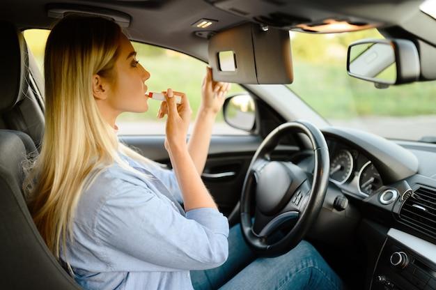 女子学生は自動車、自動車学校のレッスンで化粧をします。車を運転する女性を教える男。 Premium写真