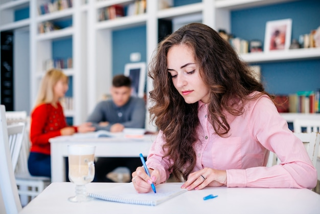 Female student making notes in notepad Free Photo