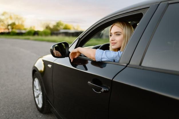 Female student poses in car, driving school Premium Photo