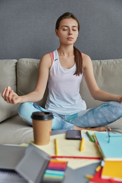 Female student sits in lotus pose, feels peace breathing, finds inspiration in meditation, drinks coffee Free Photo