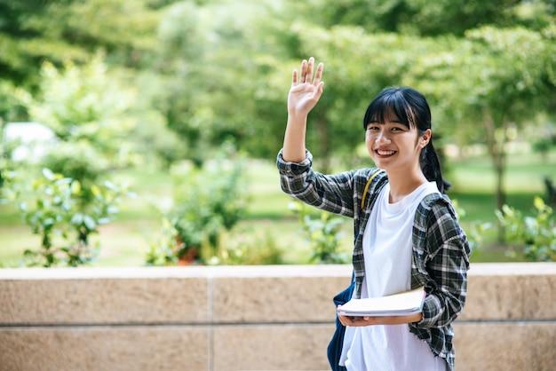 女子学生は階段の上に立ち本を持っています。 無料写真