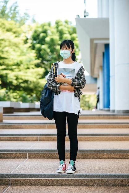 女子学生はマスクを着用し、階段の上に立ち、本を持っています。 無料写真
