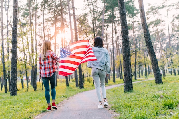 Female students with flag of usa in park Free Photo
