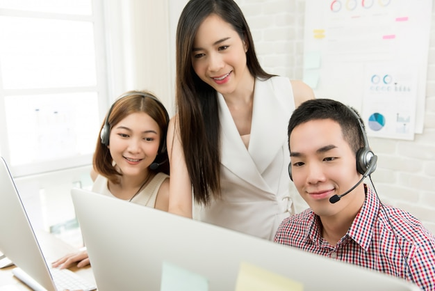 Female supervisor discussing work with telemarketing customer service agent team in call center Premium Photo