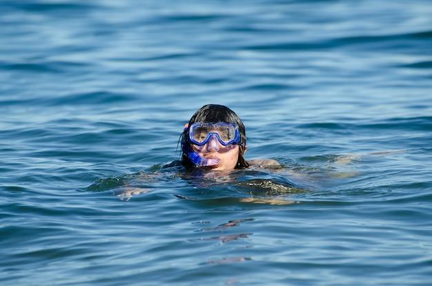 Donna che nuota in acqua con una maschera subacquea Foto Gratuite