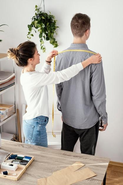 男性のクライアントのシャツを測定する女性の仕立て屋 無料写真