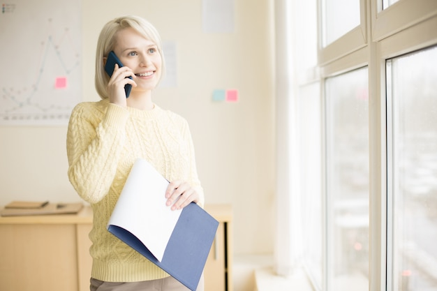 Female talking on mobile phone in office Free Photo