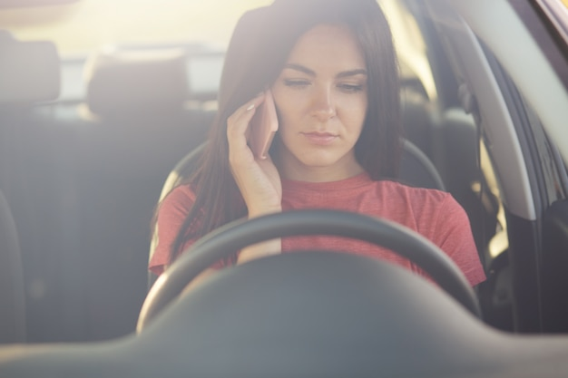 Female talks via cell phone with husband, doesn't know what to do as stops on road, has no petrol in automobile Free Photo
