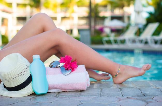 Female tanned legs near sun cream, hat, towel and sunglasses against the swimming pool Premium Photo