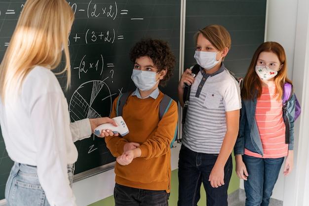 学校で子供の体温をチェックする女教師 無料写真