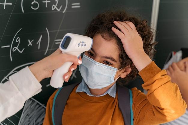 学校で生徒の体温をチェックする女教師 無料写真