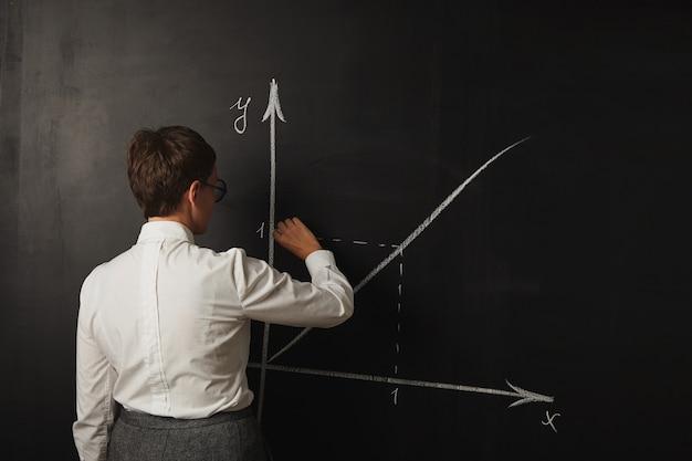 Insegnante femminile in attrezzatura conservatrice che insegna una classe di matematica alla lavagna Foto Gratuite