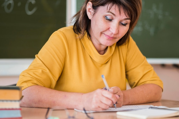 Female teacher at desk taking notes Free Photo