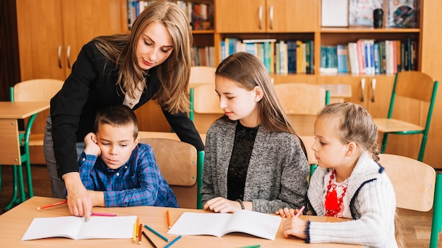 Female teacher helping pupils in studying process Free Photo