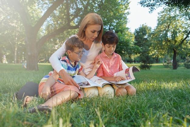 公園の芝生に座って、小さな生徒と一緒に読書をしている女教師 Premium写真