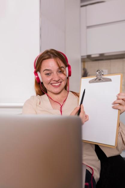 Insegnante femminile che mostra agli studenti in classe online la lezione sul blocco note Foto Gratuite