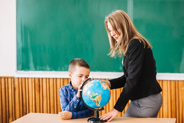 Female teacher and student boy working with globe Free Photo