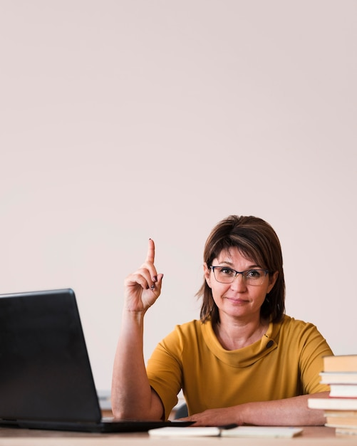 Female teacher with laptop pointing Free Photo