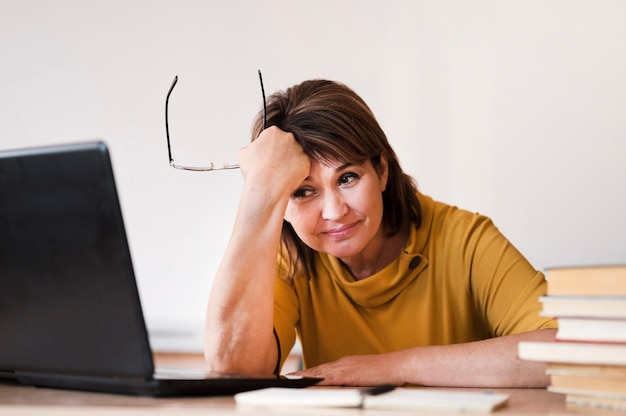 Female teacher with laptop tired Free Photo