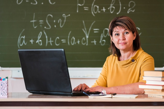 Female teacher with laptop working Free Photo