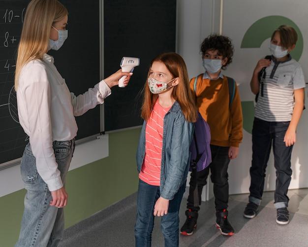 Учительница с медицинской маской проверяет температуру детей в школе Бесплатные Фотографии