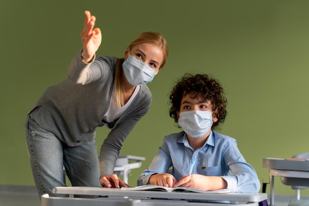 Учительница с медицинской маской объясняет урок мальчику Premium Фотографии