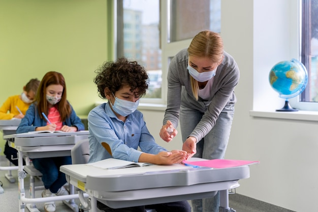 Female teacher with medical mask giving hand sanitizer to children in classroom Free Photo