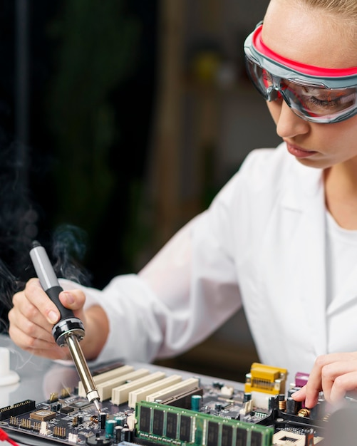Female technician with soldering iron and electronics board Free Photo
