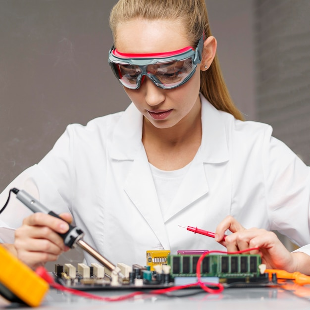Female technician with soldering iron and electronics motherboard Free Photo