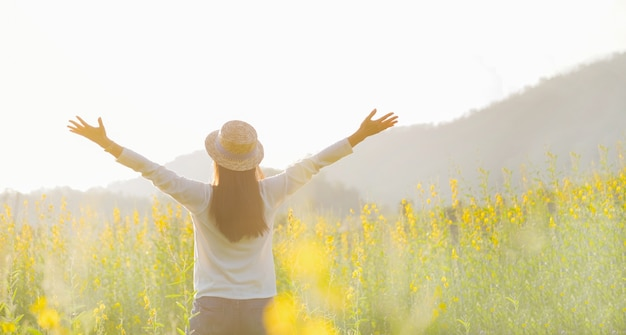 Female teen girl stand feel freedom and relaxation travel outdoor enjoying nature with sunrise. Free Photo