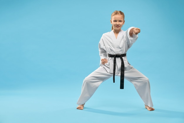 Female teenager standing in stance and punching in studio Free Photo
