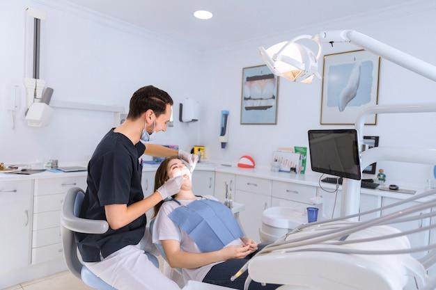 Женские зубы проверяются мужским стоматологом в клинике Premium Фотографии