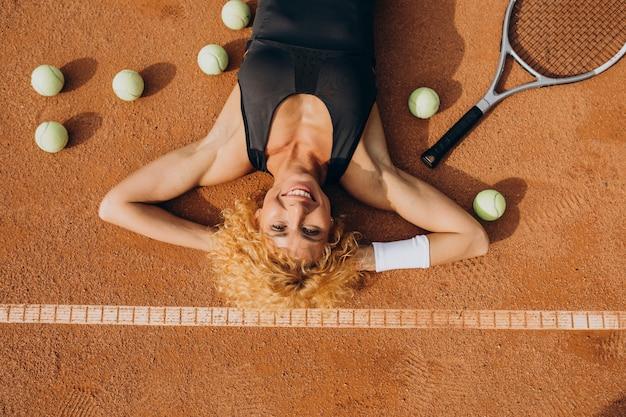 テニスコートで横になっている女性のテニス選手 無料写真