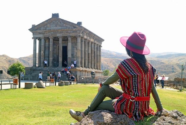 アルメニアのガルニ神殿の豪華な建築に感銘を受けた女性観光客 Premium写真