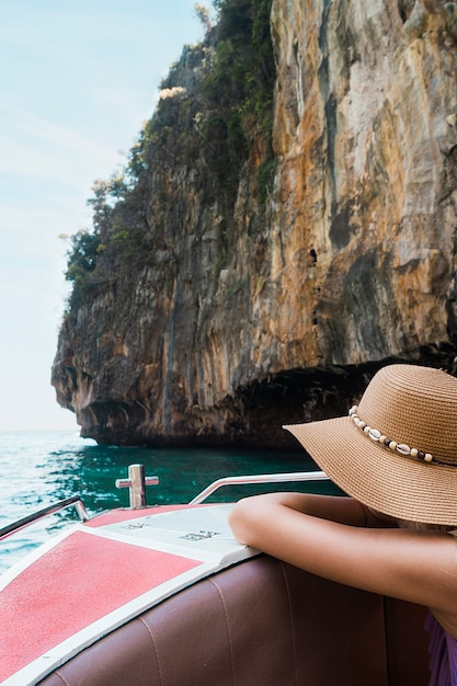 Female tourist leaning on boat travel near the cliff Free Photo