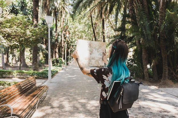 Женский турист, глядя на карту в парке Бесплатные Фотографии