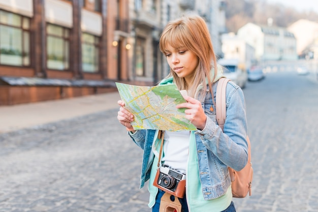 Female tourist standing on city street looking at map Free Photo