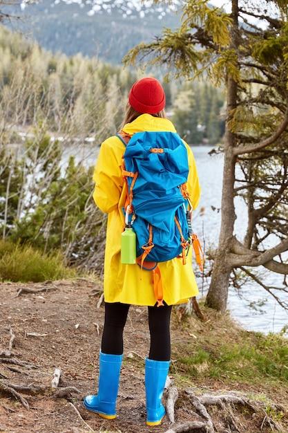 女性観光客はカメラに立ち返り、カジュアルな黄色のレインコート、ゴム長靴を着て、山の湖の近くで新鮮な空気を吸い、アクティブなライフスタイルをリードします 無料写真