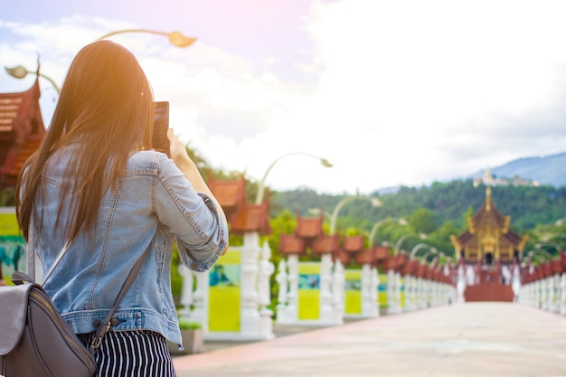Female tourist taking picture of buddhist temple in chiangmai, thailand with mobile smart Premium Photo
