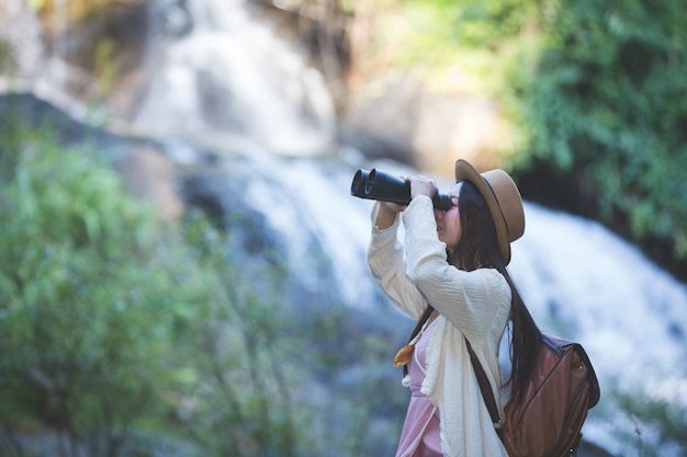 Female tourist who is looking at the binoculars to see the atmosphere at the waterfall Free Photo