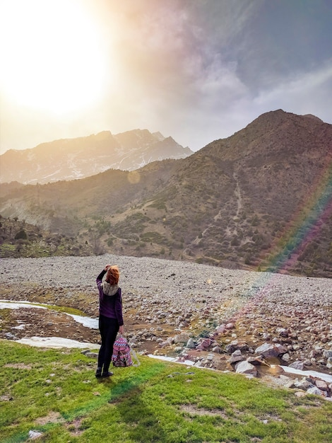Female tourist with a backpack, admiring the mountains, walking in the mountains in the su Premium Photo