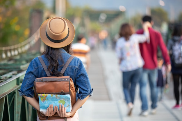 Female tourists on hand have a happy travel map. Free Photo